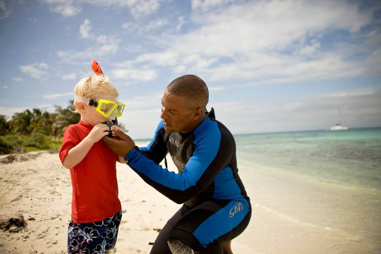 Man helping a boy with a snorkeling mask