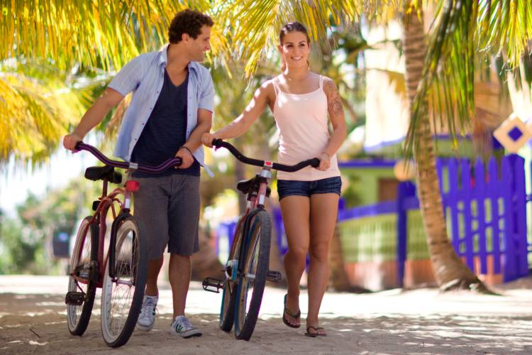 Couple walking with bike in San Pedro, Belize